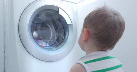 prát : Cute Child Looks Inside the Washing Machine. Cylinder Spinning Machine. Concept Laundry Washing Machine, Industry Laundry Service.