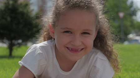 nevinný : Close Up Portrait Cute Happy Caucasian Little Girl Smiling Looking the Camera, Enjoying Warm Summer Vacation Sunny day. Dostupné videozáznamy