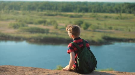 looking distance : Teenager in a red shirt with a backpack on his back, at sunset, sitting on a high hill and looking at the clouds in the sky, nature, river, trees.