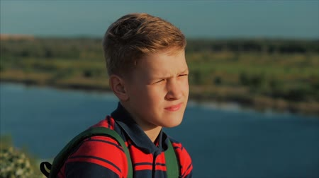 looking distance : Portrait Young Caucasian Boy Teenager in a red shirt with a backpack on his back, at sunset, sitting on a high hill enjoying warm summer vacation. Stock Footage