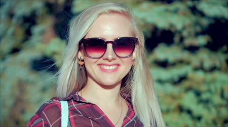 rendes : Portrait of European Cute Blonde in with Sunglass Young Happy Woman or Cheerful Girl Looking in The Camera, Blowing Wind Hair the Wind , Slow Motion.