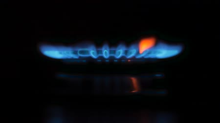gas hob : Gas stove on black background.Gas is switching on, apearing blue flame.