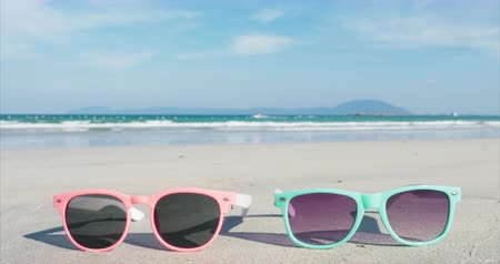 Tropical Beach Close-Up Sunglasses Pink and Blue Lie on the White Sand Against the Ocean. Wideo