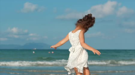 Happy Cute girl Dancing on the Tropical Coast Along the Beaches on the Background of the Tropical Ocean. Concept: Children, Happy Childhood, Summer, Child, Vacation.