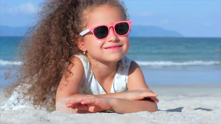 Portrait of a Beautiful Little Girl in Pink Glasses, Cute Smiling Looking at the Camera, Lying on the Sand by the Sea, Pours Sand of Hand.