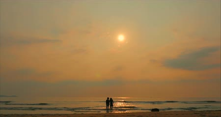 Young Couple Looking Towards the Sun, Against the Sunset, Holding Hands, Go to the Sea, a Romantic Concept on a Tropical Background.
