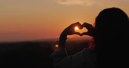 Beautiful Woman making heart shape with hands at sunset Girl holding up love symbol gesture with orange sun flare.