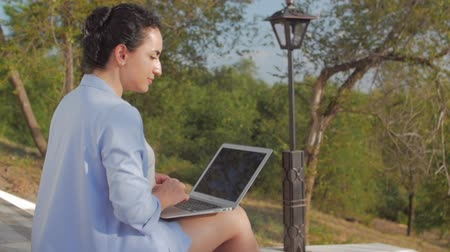 Business Woman Working on the Laptop, Attractive Brunette in a Blue Suit With a Laptop, attractive Lady working on her computer on outdoors. Wideo