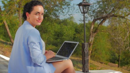 Business Lady Working on the Laptop, Attractive Brunette in a Blue Suit With a Laptop, attractive woman working on her computer on outdoors.