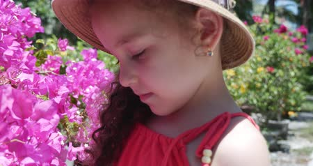 Portrait of little girl in a straw hat who is considering beautiful flower buds. Concept: baby, child, children, Childhood, Summer , freedom, kids