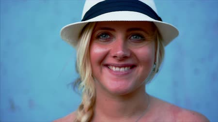 Portrait of beautiful woman caucasian blonde in white hat, smiling at camera. Cropped view, blue background, copy space