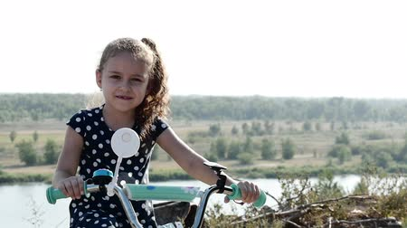 Cute little happy girl sitting on a new bike on the top of the hill, looking at the camera and smiling. Wideo