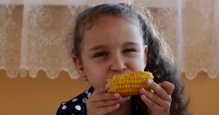 Cute little girl enjoying delicious corn on a warm summer day. Child eats boiled corn at home looking at the camera. Wideo