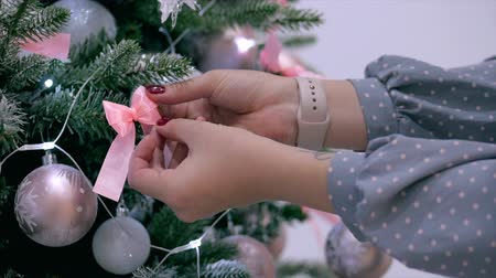 Young Hands of a woman spread a bow on the Christmas tree, decorate the festive Christmas tree with festive lights and Christmas balls.