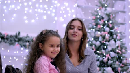 Young attractive mother and daughter sitting hugging looking at the camera smiling against the background of Christmas lights and Christmas tree. Filmati Stock