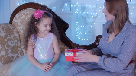opener : Young Happy Mother With Her Little Sweet Daughter Open a Gifts, Look Inward and Rejoice in the Background of the Christmas Tree.