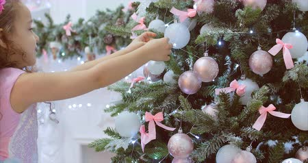 x mas : CU little girl with curly hair in a festive dress, hanging Christmas decorations on the Christmas tree with Christmas lights. Decoration on the Christmas tree with a ball. 4K