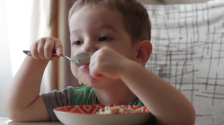 сладость : Cute little baby alone eats porridge with a spoon from a plate, the concept of healthy eating. Стоковые видеозаписи