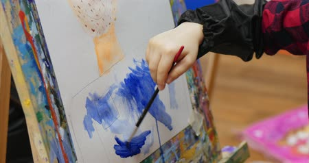 Young cute Female Artist is in an Art Studio, Sitting Behind an Easel and Painting on Canvas. Drawing Process: in the Art Studio of the Artists Hand Art Girl with a Brush Painting on Canvas. Filmati Stock