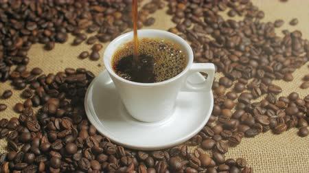 italian coffee : Coffee cup and coffee beans. White cup of evaporating coffee on the table with roasted bean. Stock footage. Stock Footage