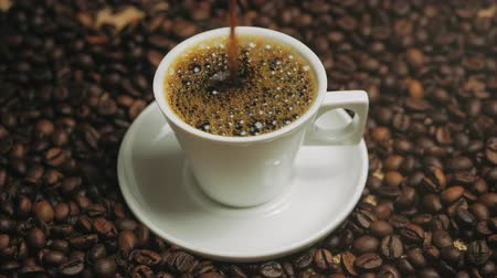 aromático : Coffee cup and coffee beans. White cup of evaporating coffee on the table with roasted bean. Stock footage. Vídeos