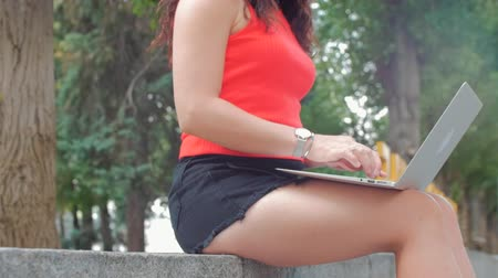 seçkinler : Woman Working on the Laptop, Attractive Brunette in a Black shorts With a Laptop work on the Park, Girl prints on her computer on outdoors. Stok Video
