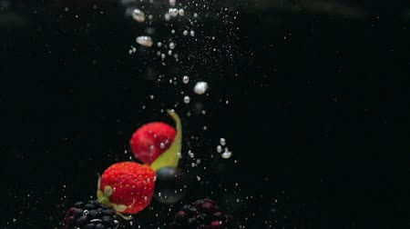 black raspberry : Fresh raspberries with blueberries and fresh mint leaves fall on a black background into the water, splashing on a black background. Drop fresh fruits and berries into the water. Healthy eating, slow motion.