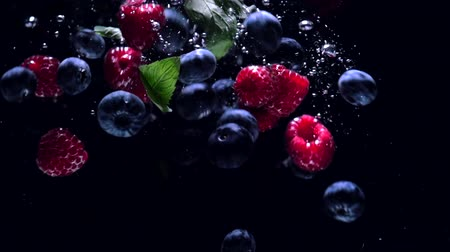 Fresh raspberries with blueberries and fresh mint leaves fall on a black background into the water, splashing on a black background. Drop fresh fruits and berries into the water. Healthy eating, slow motion.