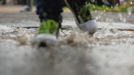 perfect weather : Close-up, Low angle, Unrecognizable Kids Running Through Puddles Summer Day After Rain. Carefree Children Run in Puddles. Concept of a Happy Childhood. Stock Footage