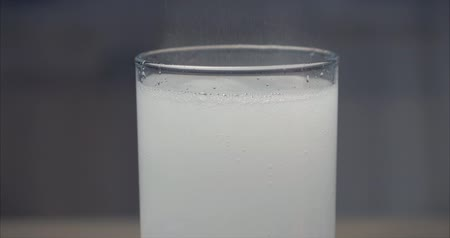 aspiryna : Two aspirin tablets fall into a glass of crystal clear water, fizzy bubbles in a glass of water. Health Concept.