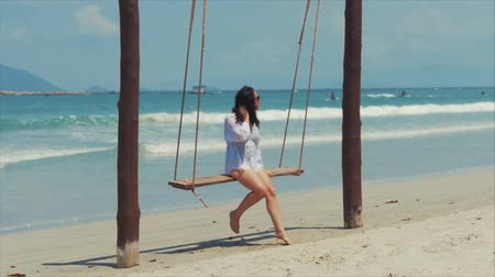 narozený : On a Tropical Beach Happy Family, European Beautiful Cute Brunette in with Sunglass Young Woman riding on a swing, Blowing Wind Hair the Wind , Slow Motion.