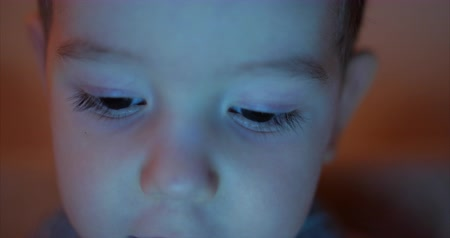 wzrok : Night picture of a happy childs face looking at a tablet PC with light reflection in his eyes. Wideo