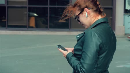 凝視 : Young Woman Typing Texting a Mobile Phone on the Street, While Walking in an Urban Setting.
