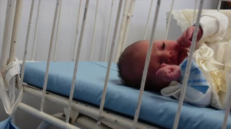 caring : Newborn baby lying in bed after childbirth, looking at the camera. Concept of the Hospital. Stock Footage
