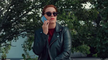 collaborating : Young Woman in sunglasses talking a Mobile Phone on the Street, While Walking in an Urban Setting. Stock Footage