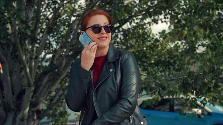 collaborating : Young woman in sunglasses talking on the mobile phone while sitting in the Park on a bench, records of conversation in notes on a tablet. Girl talking on the phone. Stock Footage