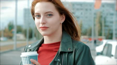 jó hangulatban : Young Woman Drinking Coffee on the Street, Young Girl With Glasses of a Happy Woman with Long Red Hair in a Good Mood, Positive Emotions.