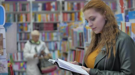 prateleira de livros : Portrait of a Young Beautiful Woman with Bright Red Hair in Glasses, Pretty Girl Reading in Book Library University. Stock Footage