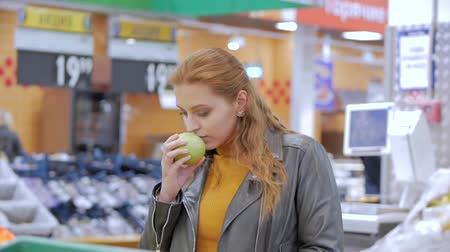 апельсины : Pretty young beautiful red hair woman buys food, fruits, apples, tomatoes, oranges in the market, in the supermarket.Girl chooses products,vegetables, fruits in the store.Shopping,Vegan sales concept.