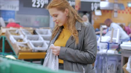 апельсины : Pretty young beautiful red hair woman buys food, fruits, apples in the market, in the supermarket.Girl chooses products,vegetables, fruits in the store.Shopping,Vegan sales concept. Стоковые видеозаписи