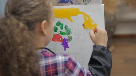 холст : Drawing process: in the artists art Studio, hand girl with a brush painting on canvas. Childrens hand of the artist gaining paint on the brush, sitting at the easel in the Studio and draws on canvas. Стоковые видеозаписи