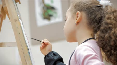 cavalete : Young Hands of the Artist, Little Girl Artist Paints a Canvas with Brush,Sitting a Table and Draw on Canvas. Process of Drawing: in Artists Art Studio Hand Baby Girl Sketching on Canvas.