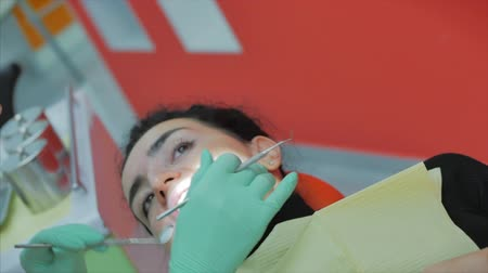 limpar : Female dentist treating patient teeth at clinic. Female professional dentist shows which teeth the patient needs to be treated. Dental examination concept. Vídeos