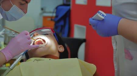 fenyegetés : Woman Dentist Treating Teeth to Woman Patient in Clinic. Female Professional Doctor Stomatologist at Work. Concept Dental Check Up.