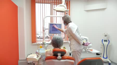 yenirce : Woman Dentist Treating Teeth to Woman Patient in Clinic. Dentist shows the patient on the tablet how the teeth will be treated, gives lessons on the proper care of teeth and the oral cavity.