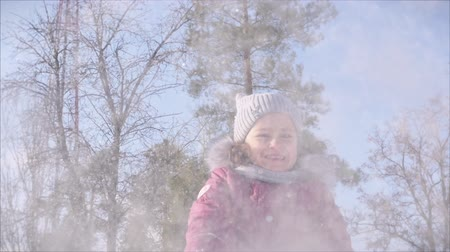 snow angel : Happy, fun childhood on a Sunny winter day outdoors. Daughter plays with the father in snowballs, throws a snow globe directly into the camera, while having fun and smiling looks at the camera. Stock Footage