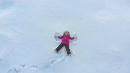 snow angel : Happy little daughter making angels in the snow. Happy, fun childhood on a Sunny winter day outdoors.