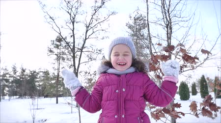 snow angel : Happy, Fun Childhood on a Sunny Winter Day Outdoors. Happy Little Girl While Having Fun and Smiling Looks At the Camera. Stock Footage