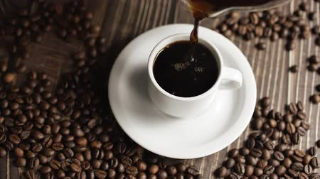 dark roast : Coffee cup and coffee beans. White cup of evaporating coffee on the table with roasted bean. Slow Motion coffee pour. Stock Footage