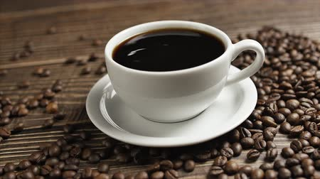 dark roast : Coffee cup and coffee beans. On a wooden table is a white mug of coffee and coffee beans are lying around, close-up drops of coffee falling into a cup.